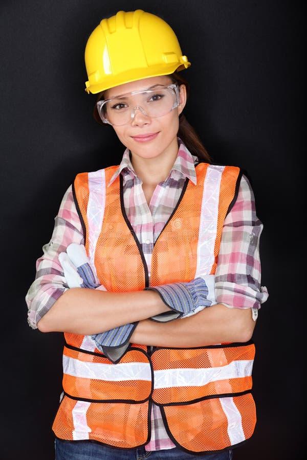 Byggnadsarbetare med säkerhetskugghjulet på svart royaltyfri fotografi