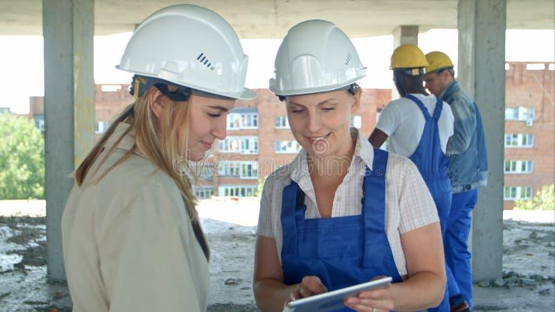Byggnadsarbetare och tekniker som arbetar på byggnadsplats, genom att använda den digitala minnestavlan royaltyfria foton