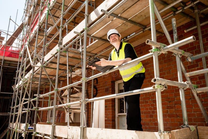 Byggnadsarbetare, ordförande eller arkitekt på materialet till byggnadsställning på konstruktionsplatsen med skrivplattan fotografering för bildbyråer