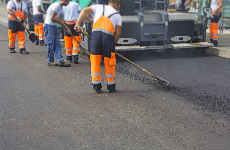 Byggnadsarbetare på att asfaltera arkivbild