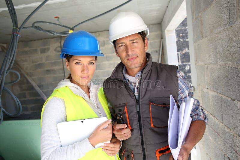 Byggnadsarbetare på byggnadsplats med minnestavlan royaltyfria foton