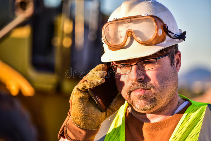 Byggnadsarbetare på mobiltelefonen royaltyfri fotografi
