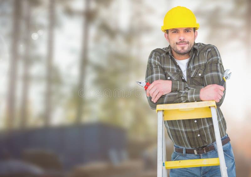 Byggnadsarbetare på stege framme av konstruktionsplatsen arkivfoto