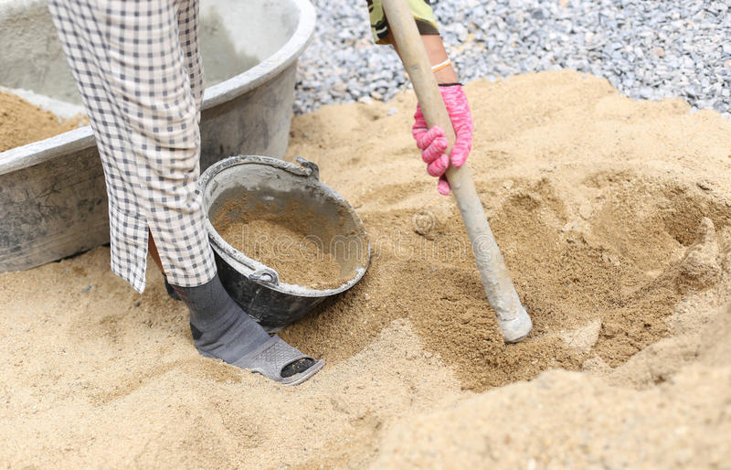 Byggnadsarbetare sätter sand i sandhinken royaltyfria foton