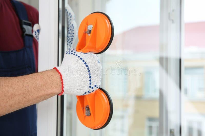 Byggnadsarbetare som använder suglyftarmen under fönsterinstallation, closeup royaltyfri bild