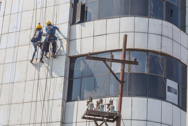 Byggnadsarbetare som arbetar på byggnaden med säkerhetshjälpmedel royaltyfria foton