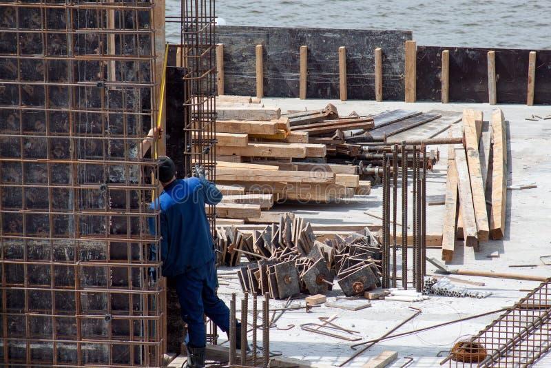 Byggnadsarbetare som arbetar på cementformworkramar royaltyfri fotografi