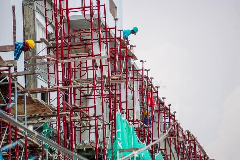 Byggnadsarbetare som arbetar på det röda materialet till byggnadsställning arkivbild