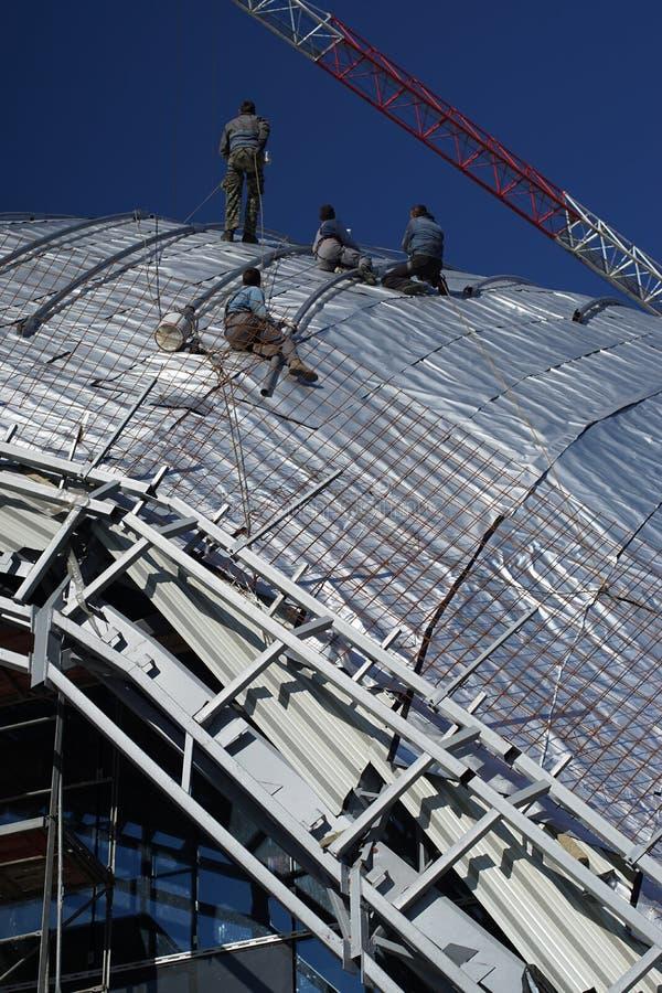 Byggnadsarbetare som arbetar på taket av en byggnad som binds med arkivbilder