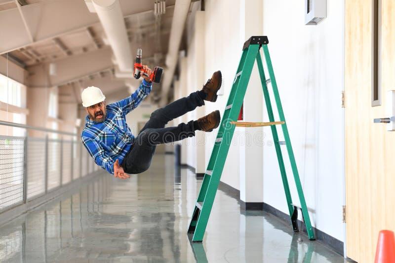 Byggnadsarbetare som av faller stegen arkivbild