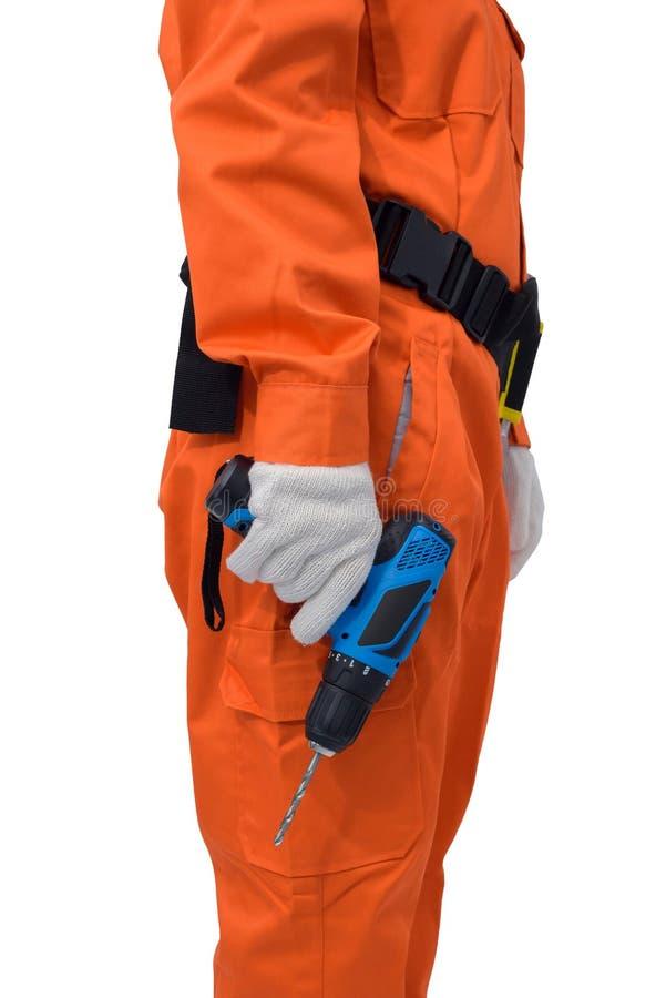 Byggnadsarbetare som bär orange skyddande kläder, hjälmhand som rymmer den elektriska drillborren med hjälpmedelbältet som isoler royaltyfria foton