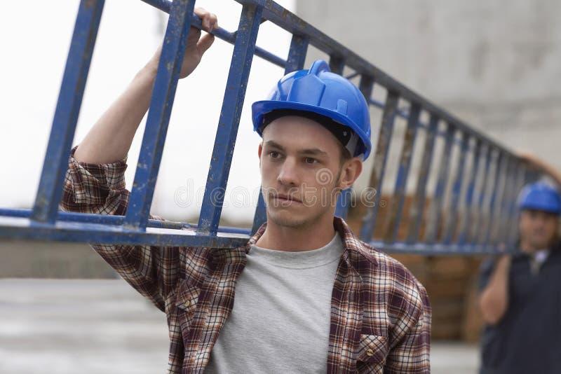 Byggnadsarbetare som bär stegen arkivbild