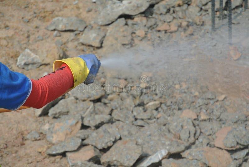 Byggnadsarbetare som besprutar den kemiska behandlingen för anti-termit till höglocket royaltyfria foton