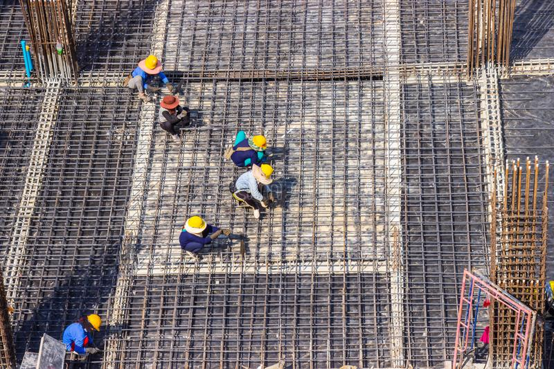 Byggnadsarbetare som fabricerar den stora stången för förstärkning för stålstång på i plats för konstruktionsområdesbyggnad arkivbilder
