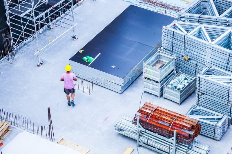 Byggnadsarbetare som fabricerar stålförstärkningstången på konstruktionsplatsen royaltyfri foto
