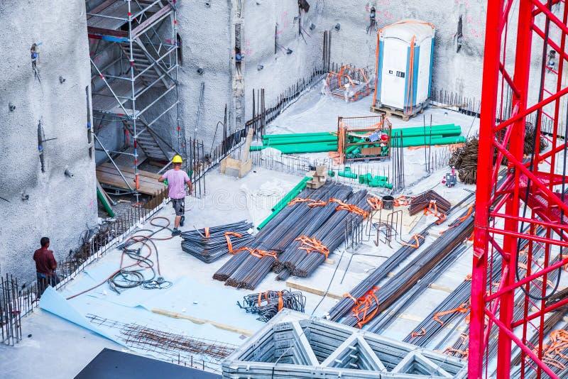Byggnadsarbetare som fabricerar stålförstärkningstången på konstruktionsplatsen arkivbild