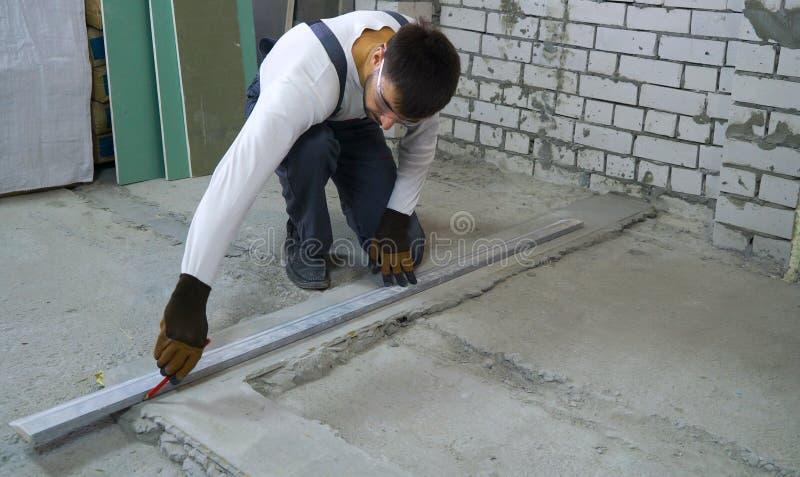 Byggnadsarbetare som gör vinst med att mäta normal på konstruktionsplatsen royaltyfri bild