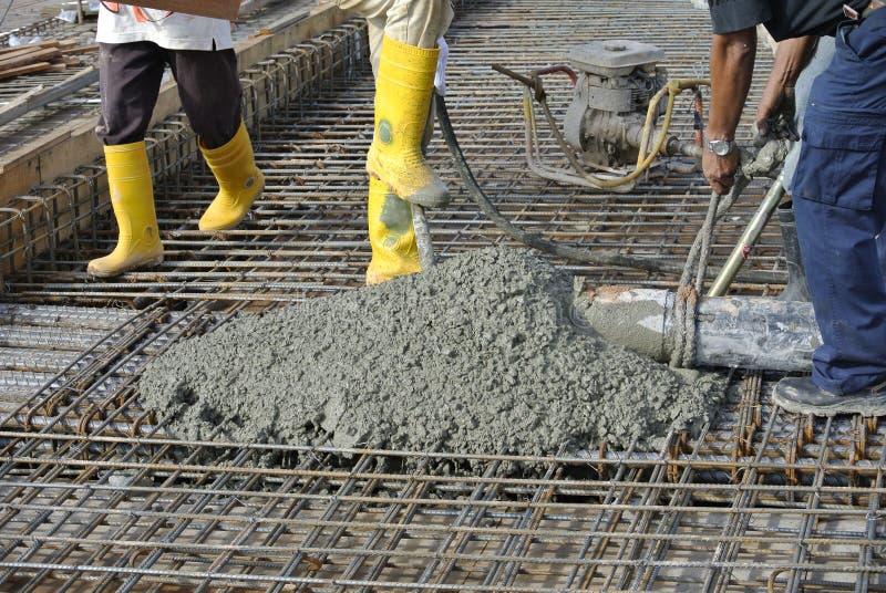 Byggnadsarbetare som gjuter betong genom att använda den konkreta slangen arkivfoto