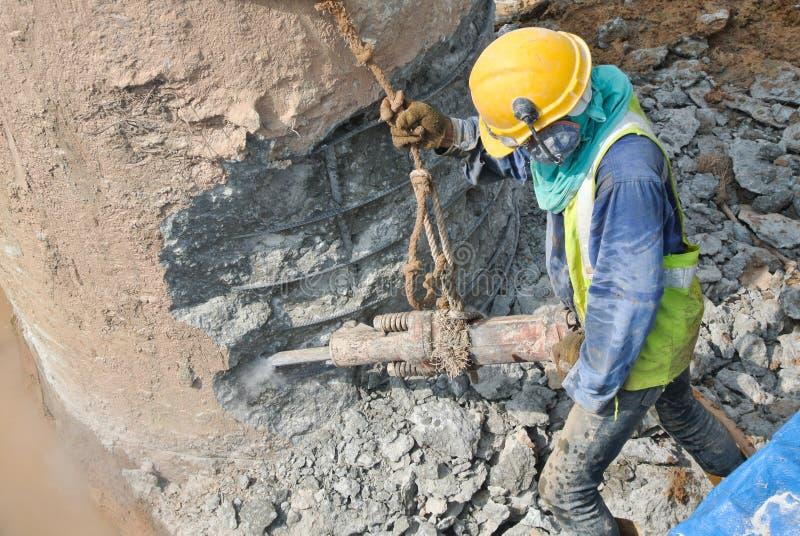 Byggnadsarbetare som hackar fundamenthögen arkivbild