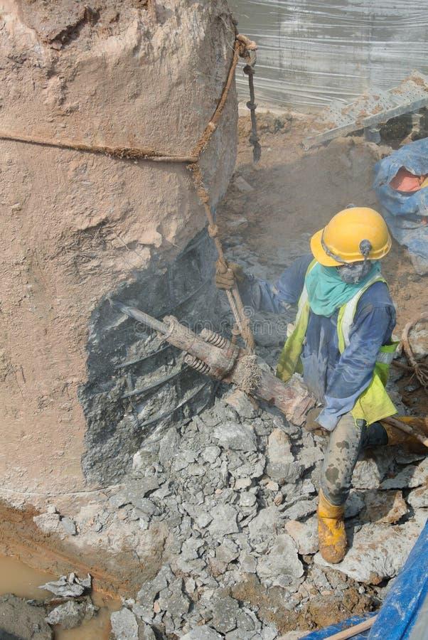 Byggnadsarbetare som hackar fundamenthögen royaltyfri fotografi