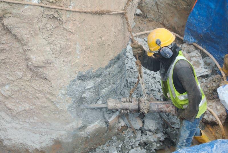 Byggnadsarbetare som hackar fundamenthögen royaltyfri foto