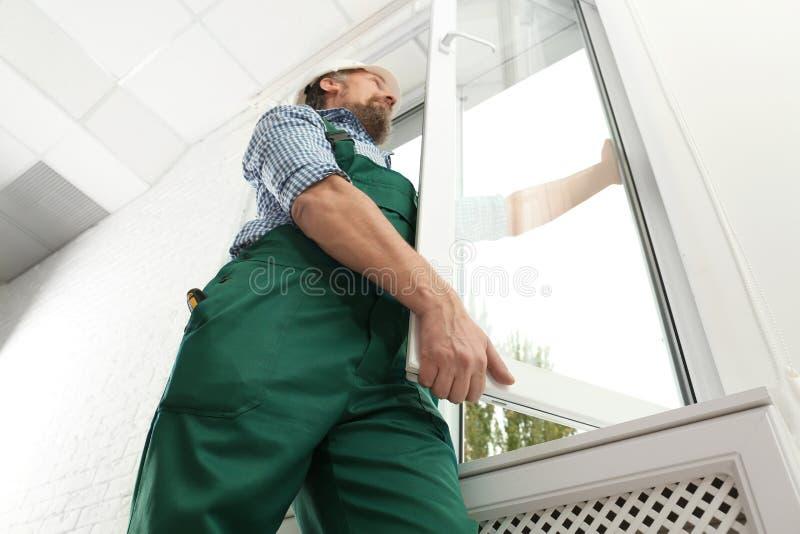 Byggnadsarbetare som installerar det nya fönstret royaltyfri fotografi