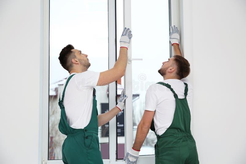 Byggnadsarbetare som installerar det plast- fönstret arkivfoto