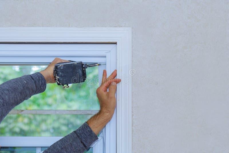 Byggnadsarbetare som installerar fönstret i hus royaltyfri fotografi