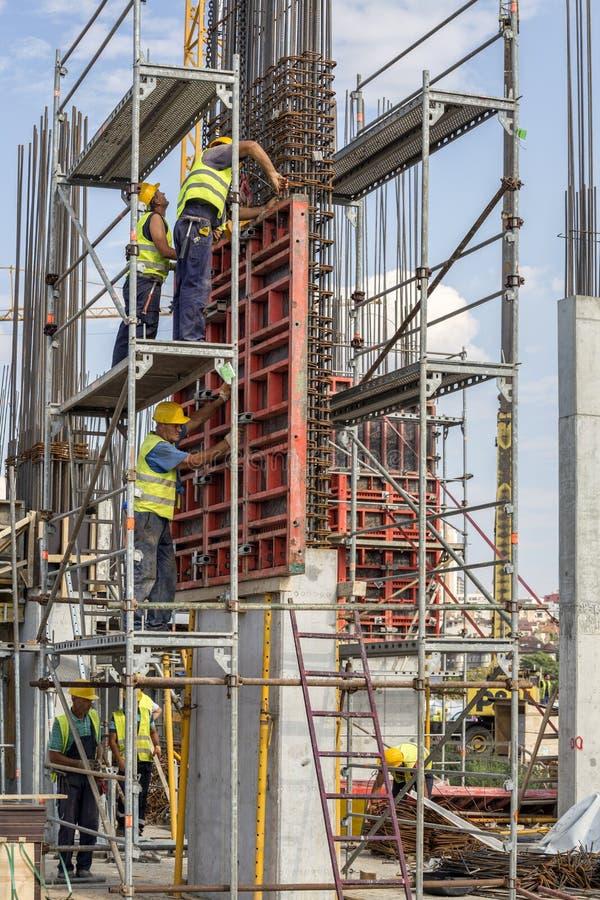 Byggnadsarbetare som installerar formen för konkret pelare royaltyfri fotografi