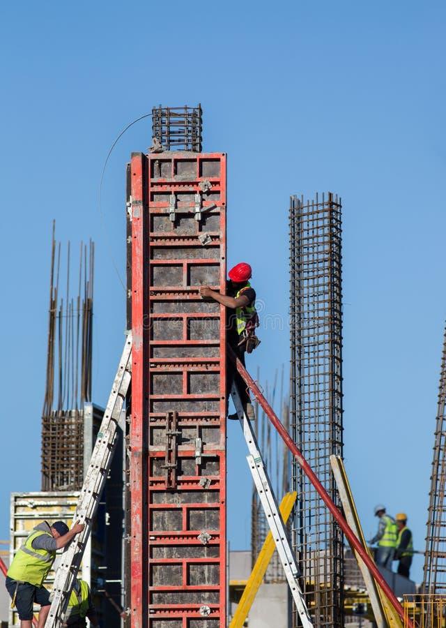 Byggnadsarbetare som installerar formwork på plats royaltyfri fotografi