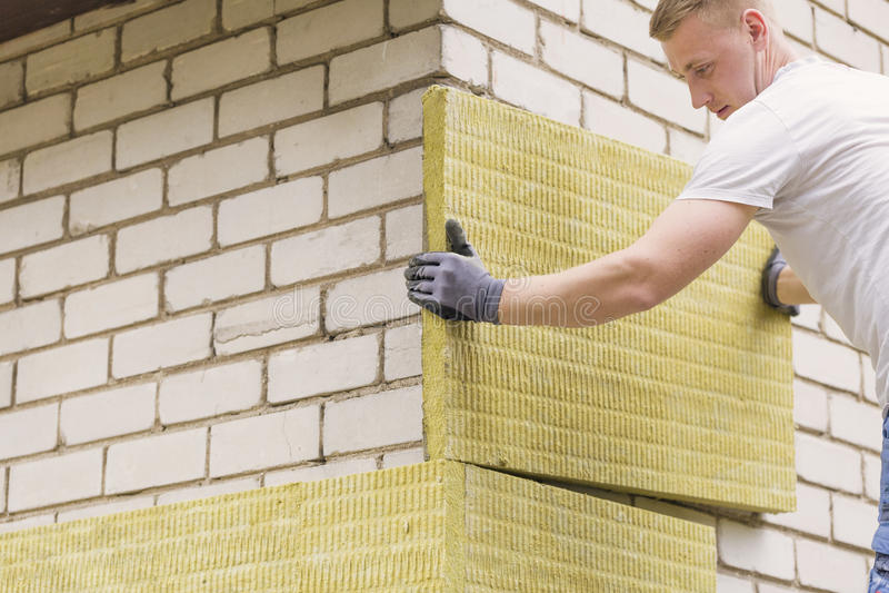 Byggnadsarbetare som isolerar husfasaden med mineral wo arkivfoton