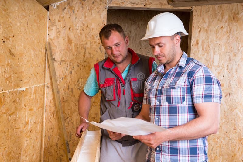Byggnadsarbetare som konsulterar plan i nytt hem arkivfoto