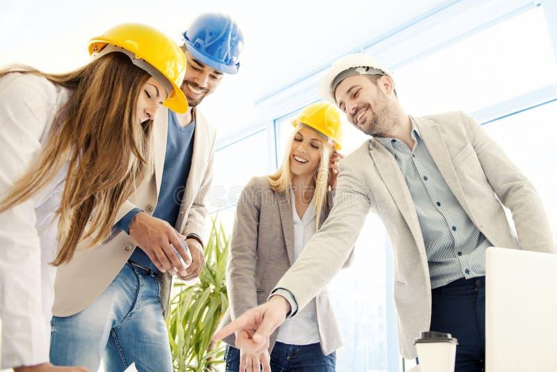 Byggnadsarbetare som kontrollerar de arkitektoniska planen för royaltyfri foto