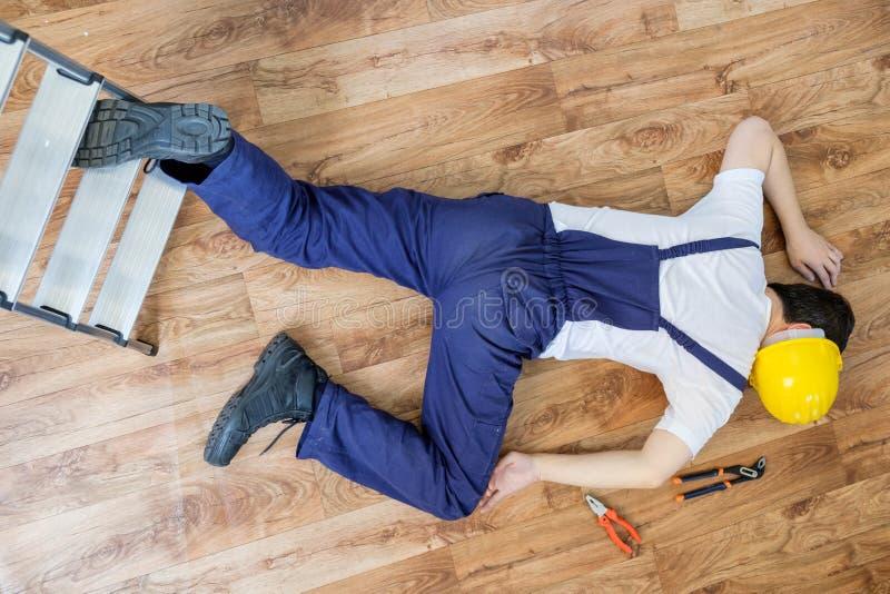 Byggnadsarbetare som ner faller stegen arkivbild