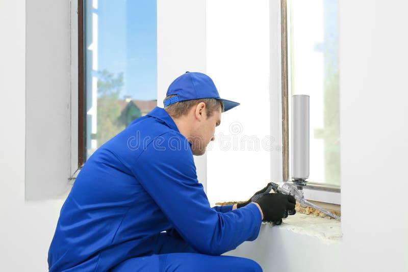 Byggnadsarbetare som reparerar fönstret royaltyfri fotografi