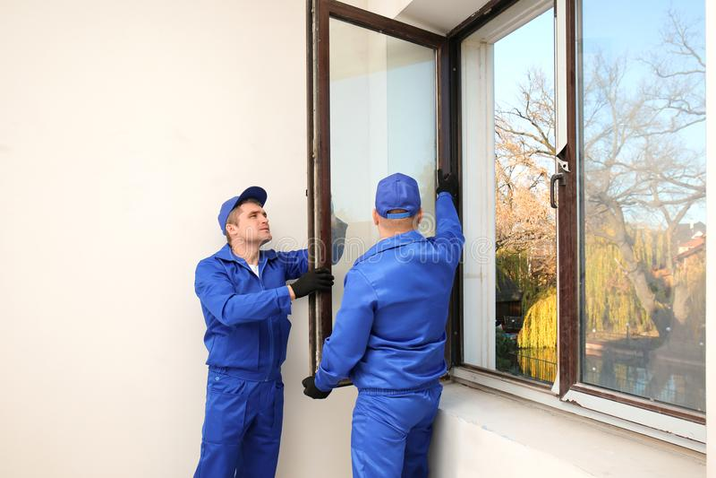 Byggnadsarbetare som reparerar fönstret royaltyfri bild