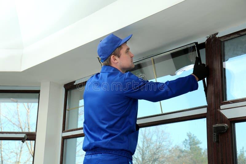Byggnadsarbetare som reparerar fönstret royaltyfria foton