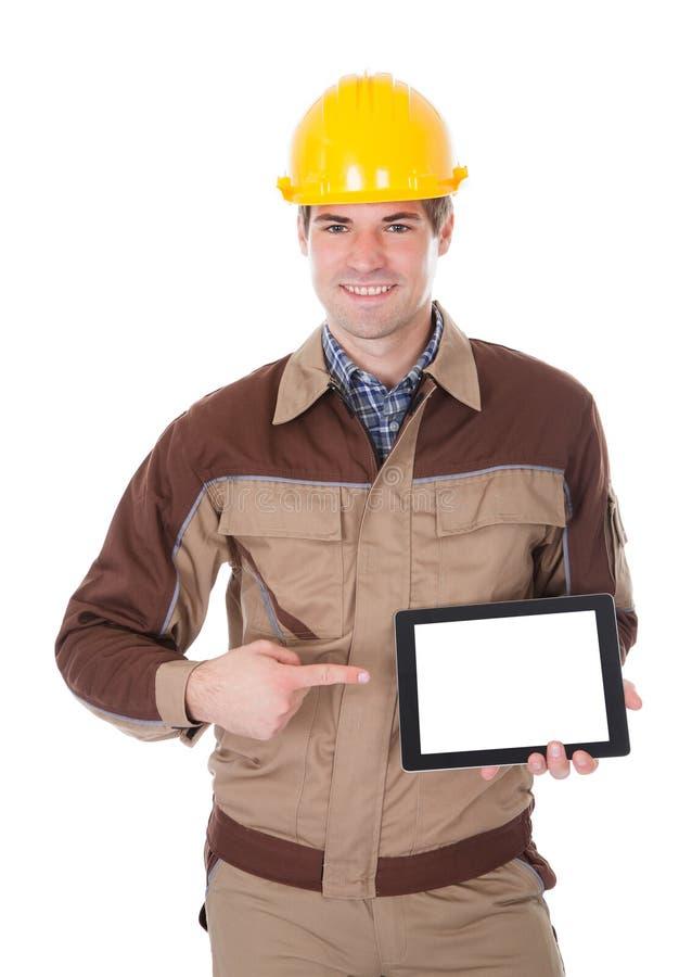 Byggnadsarbetare som rymmer den digitala minnestavlan arkivfoton