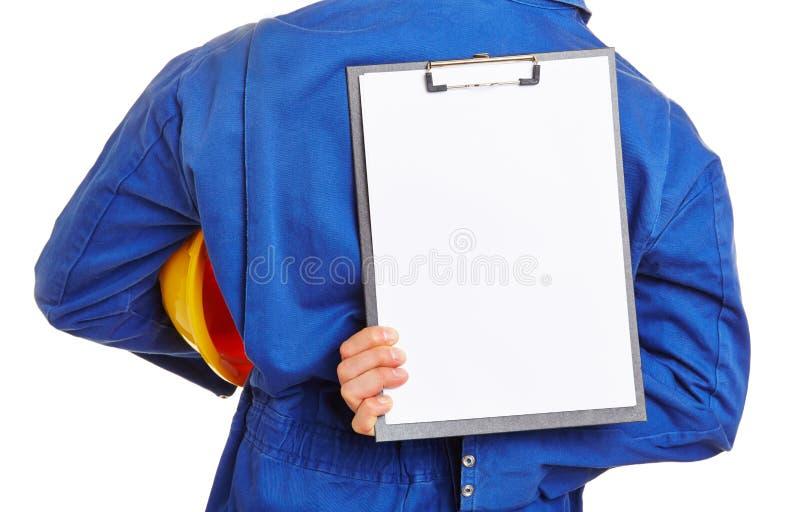 Byggnadsarbetare som rymmer den tomma skrivplattan royaltyfria bilder