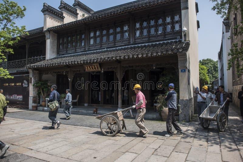 Byggnadsarbetare som skjuter vagnar för att transportera material i Laomendong sceniskt område royaltyfria foton