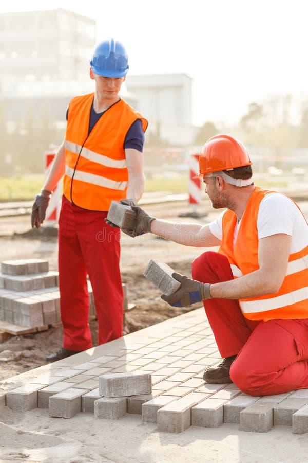 Byggnadsarbetare som stenlägger gatan royaltyfria foton