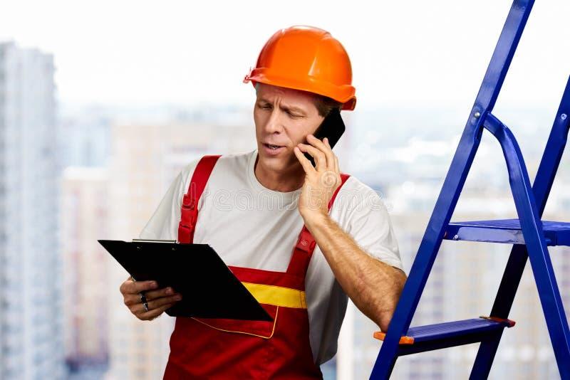 Byggnadsarbetare som talar på smartphonen royaltyfri fotografi