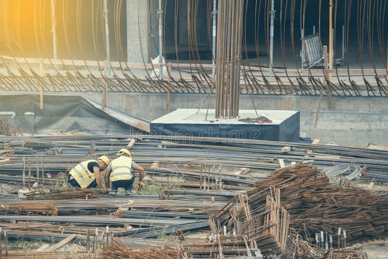 Byggnadsarbetare som väljer och mäter järnstänger royaltyfri bild