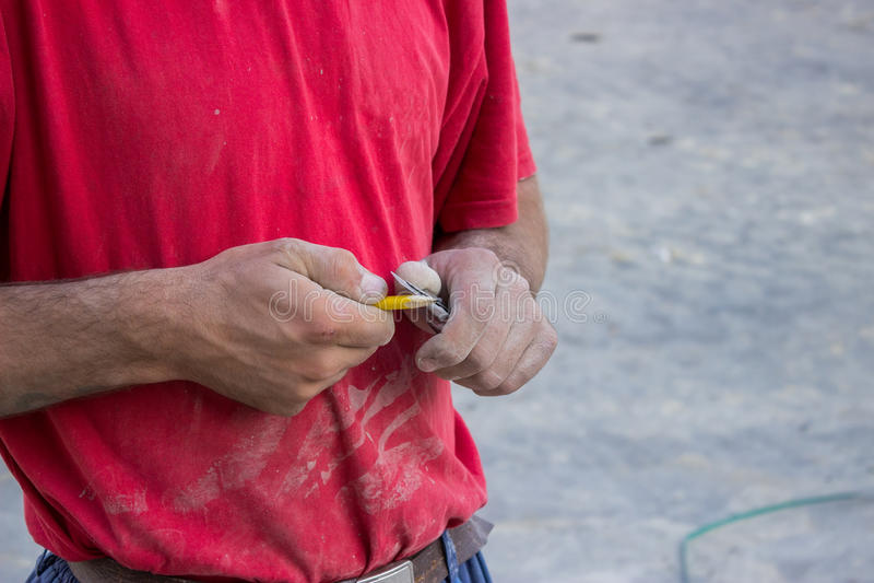 Byggnadsarbetare som vässar en blyertspenna med en kniv arkivfoton