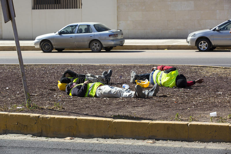 Byggnadsarbetare som vilar på gatan på lunchtime arkivbild