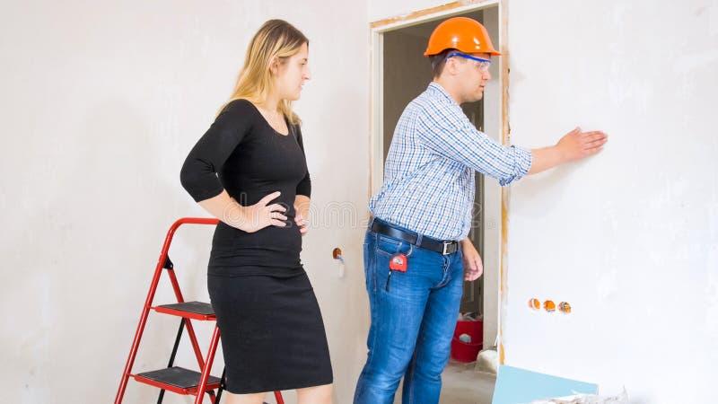 Byggnadsarbetare som visar det nya huset till den härliga unga affärskvinnan royaltyfri bild