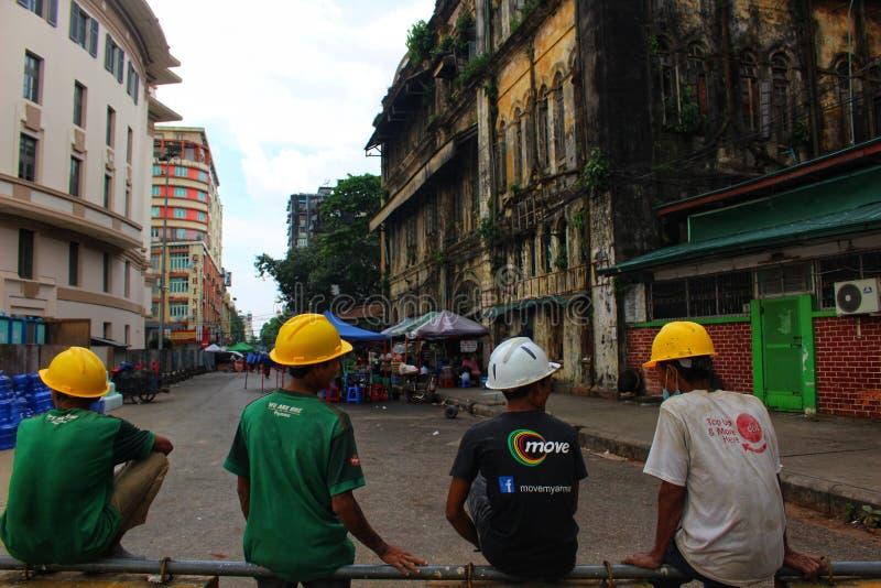Byggnadsarbetare tar ett avbrott under färgrika koloniala byggnader i i stadens centrum Yangon royaltyfri foto