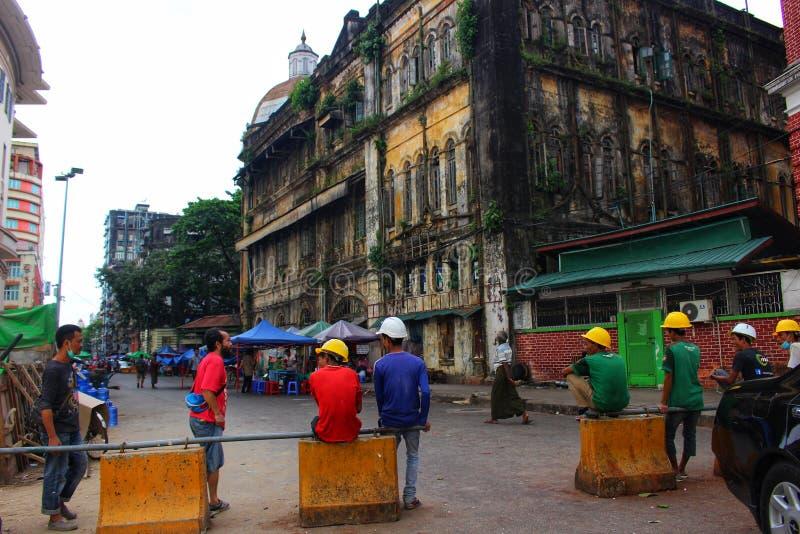 Byggnadsarbetare tar ett avbrott under koloniala byggnader i i stadens centrum Yangon royaltyfria bilder