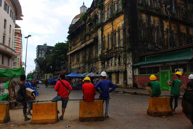 Byggnadsarbetare tar ett avbrott under koloniala byggnader i i stadens centrum Yangon arkivbilder
