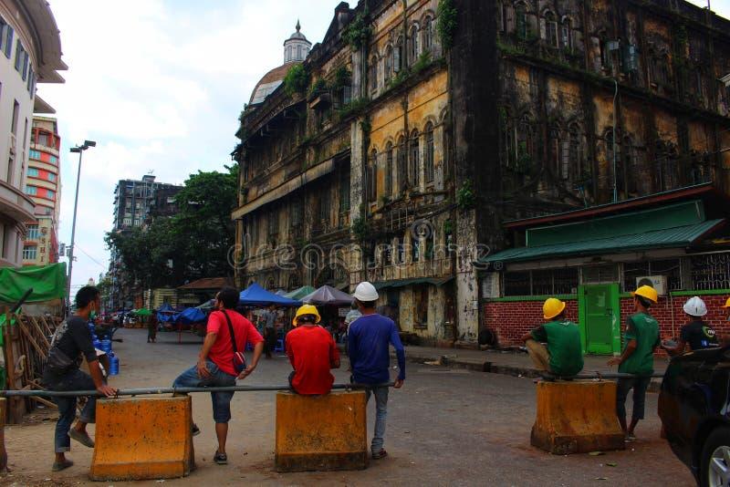 Byggnadsarbetare tar ett avbrott under koloniala byggnader i i stadens centrum Yangon royaltyfri foto
